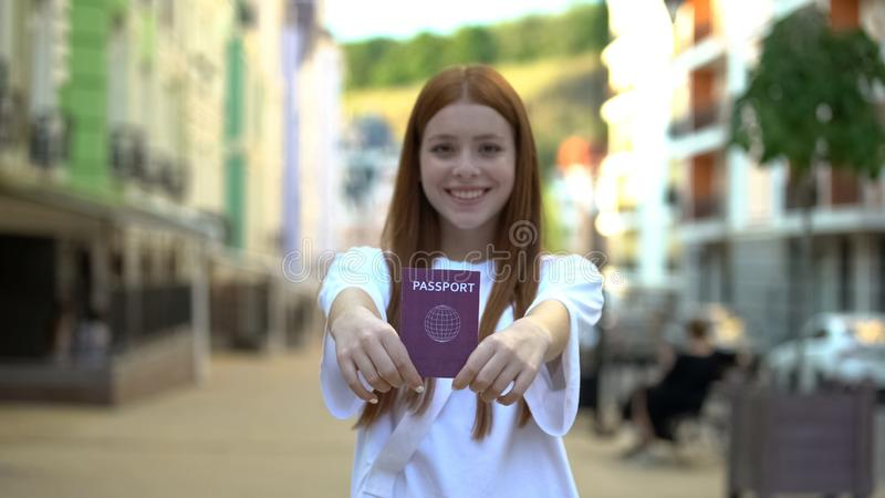 Cheerful girl showing international passport to camera, opportunities for travel stock photo