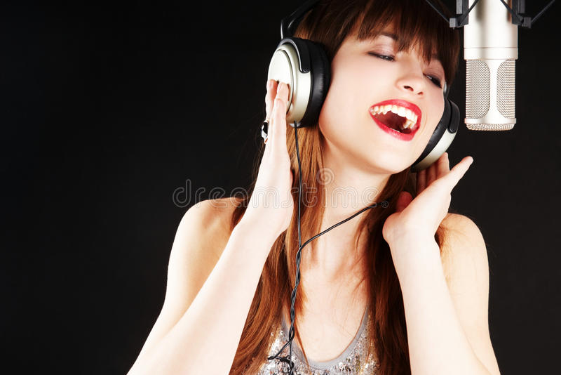 Cheerful girl singing to the microphone stock photo