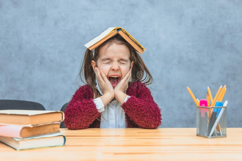 A cheerful girl sitting and holding a book over her head over a gray background. During this schoolgirl, her eyes closed. Opening her mouth yawning. He put his stock photography