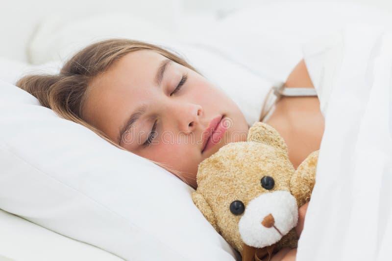 Cheerful girl sleeping with her teddy bear royalty free stock photo