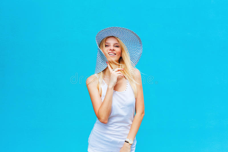 Cheerful girl smilling on a blue background with a hat royalty free stock photography