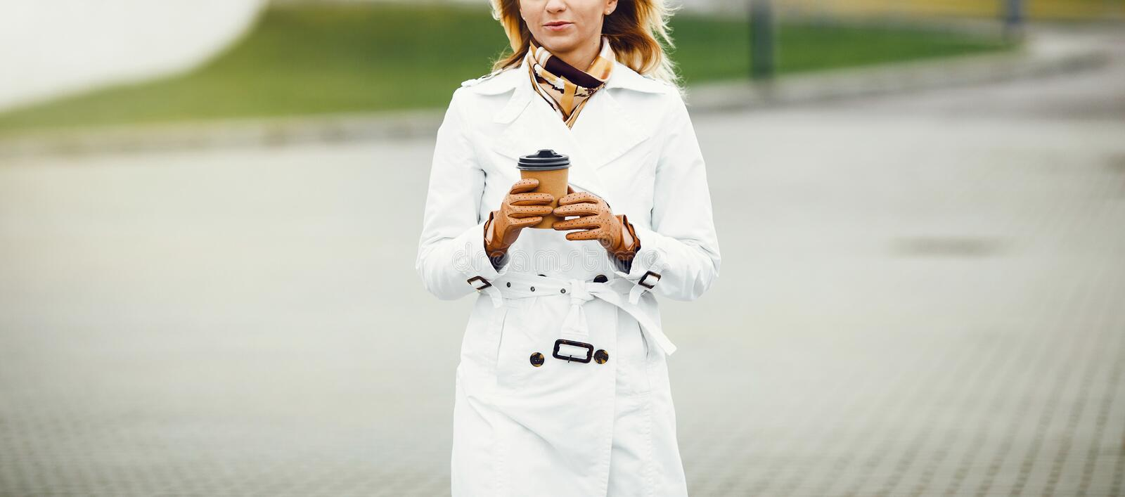 Young stylish pretty woman posing in the city streets and using stock photo