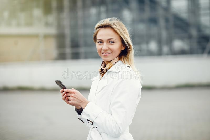 Young stylish pretty woman posing in the city streets and using royalty free stock photography