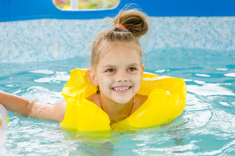 Cheerful girl swimming in pool swimming vest. Six year old girl Europeans bathed in a small suburban pool stock photo