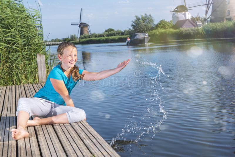 Cheerful girl  tourist splashing in the river on the beautiful landscape backgorund with old windmills in Netherlands royalty free stock photo