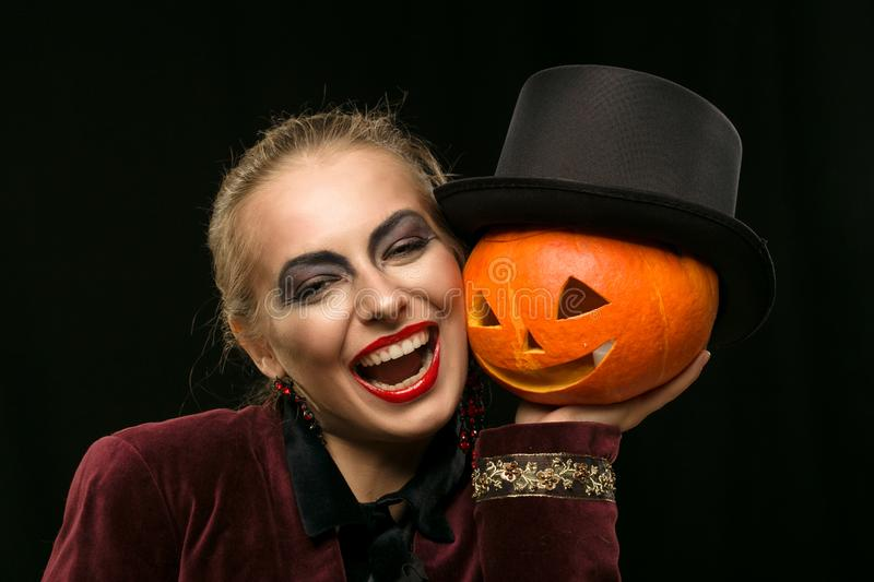 Cheerful girl witch on Halloween with pumpkin. royalty free stock image