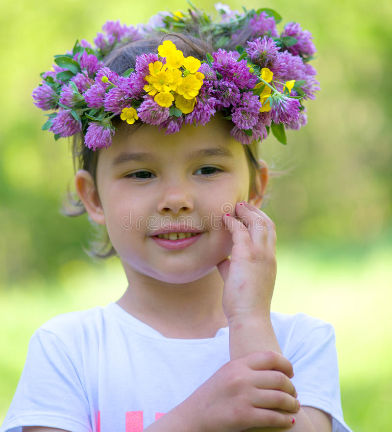 Cheerful girl with a wreath of flowers on her head royalty free stock photos