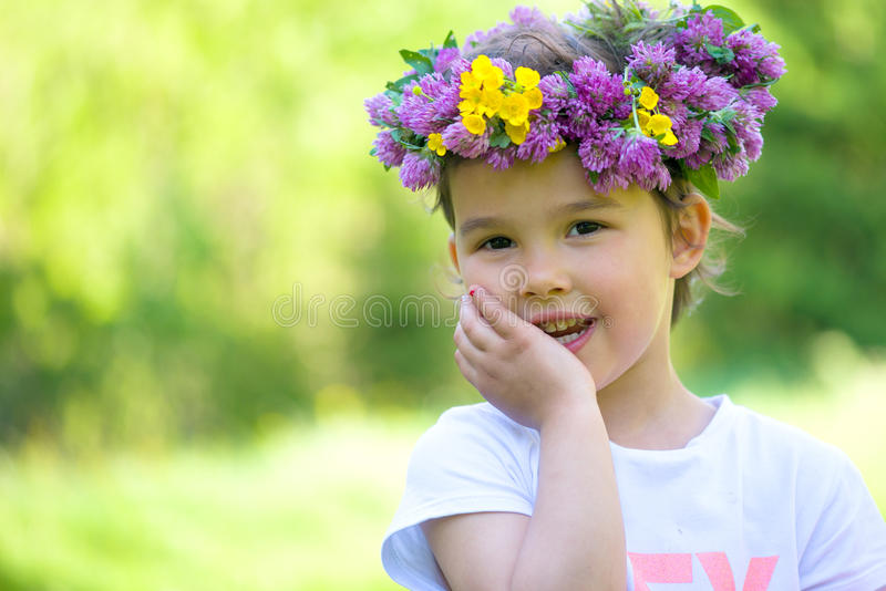 Cheerful girl with a wreath of flowers on her head royalty free stock photo