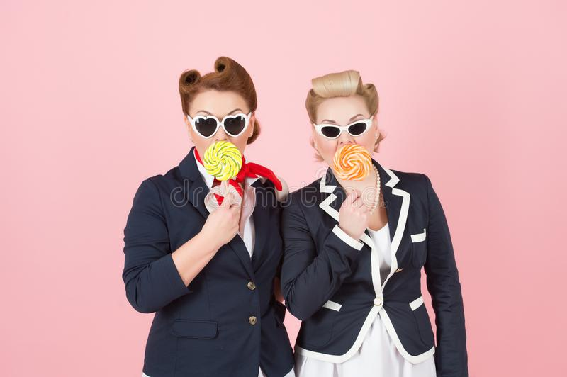 Cheerful girls couple with lollipops and glasses. Girls hide mouth by lollipops and eyes by black sun glasses. royalty free stock image