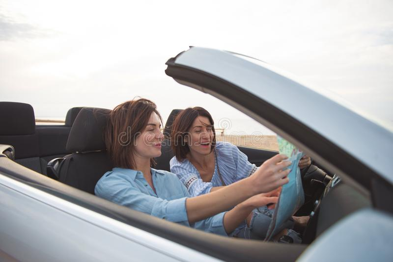 Cheerful girls are driving car stock photography