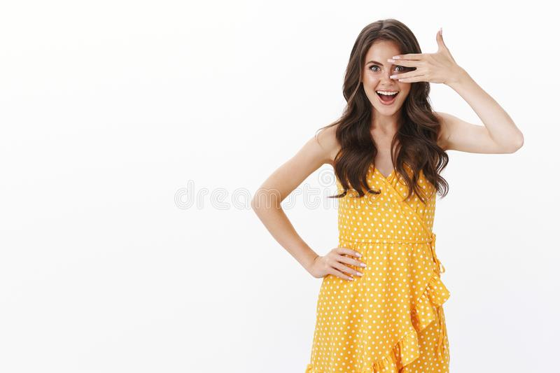 Cheerful glad excited young feminine woman in yellow casual dress, curly hairstyle, cover one eye peek through fingers royalty free stock photo
