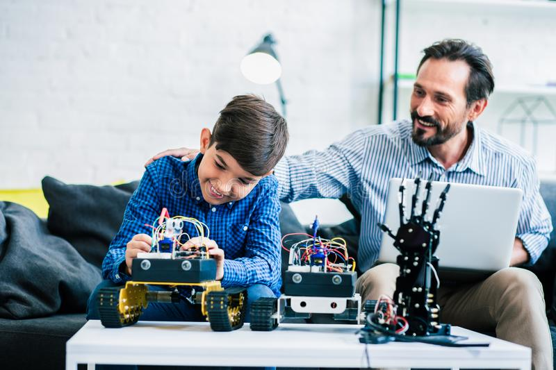 Cheerful good father helping his son with engineering project royalty free stock photo