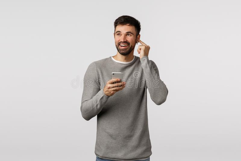 Cheerful good-looking, amazed caucasian guy enjoy awesome sound quality of headphones, put wireless earphones, increase stock images
