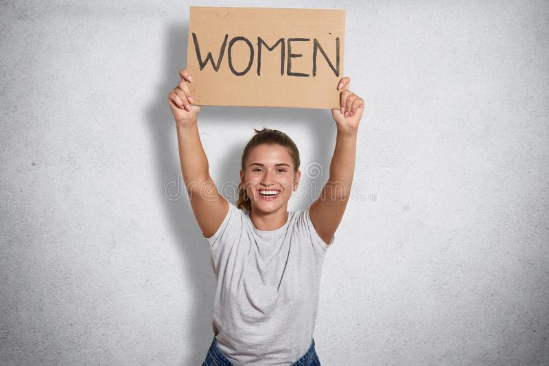 Cheerful good looking feminist smiling sincerely, raising inscription women in both hands, ready to public activity, peaceful. Cheerful good looking feminist stock images