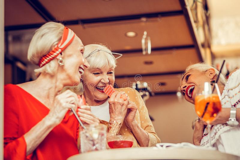 Cheerful good-looking ladies being in great mood while playing card games royalty free stock image
