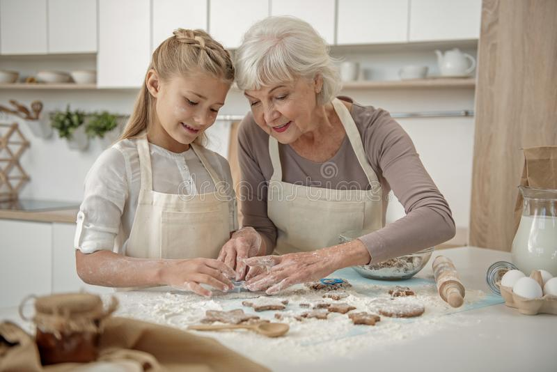 Cheerful grandchild learning to make pastry in kitchen royalty free stock photography