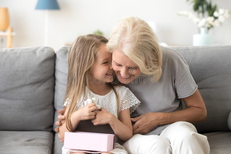 Cheerful grandma and grandchild sitting laughing together on couch stock image