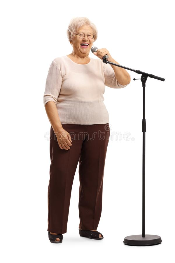 Cheerful grandmorther standing in front of a microphone. Full length portrait of a cheerful grandmorther standing in front of a microphone isolated on white stock photography