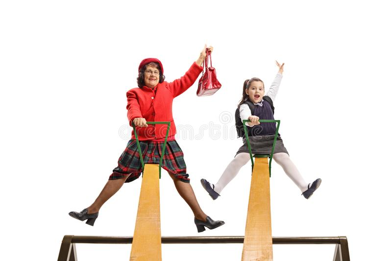 Cheerful grandmother and granddaughter having fun on a seesaw stock photo
