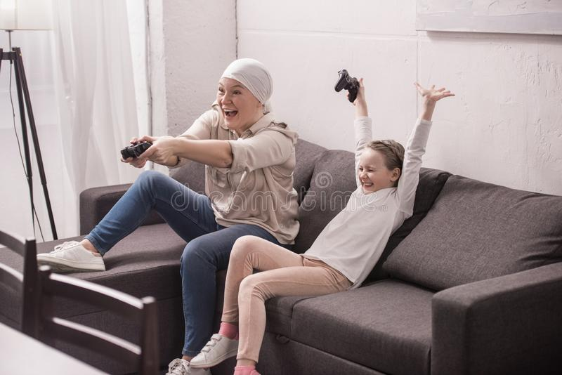 cheerful grandmother and granddaughter playing with joysticks cancer concept stock photo