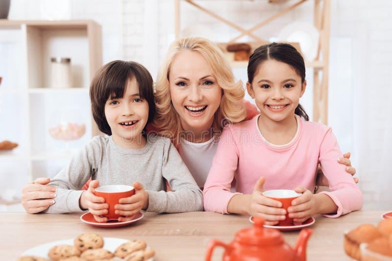 Cheerful grandmother hugs happy grandchildren drinking tea in kitchen. royalty free stock photo
