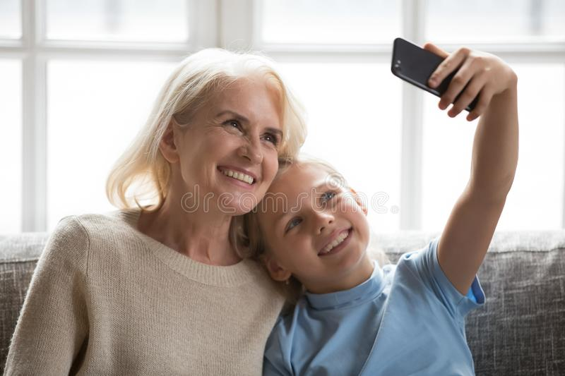 Cheerful grandmother and little granddaughter using phone taking selfie. Happy elderly grandmother and little granddaughter using phone taking selfie royalty free stock photo