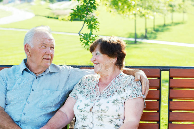 Cheerful grandparents. Sitting in park stock images