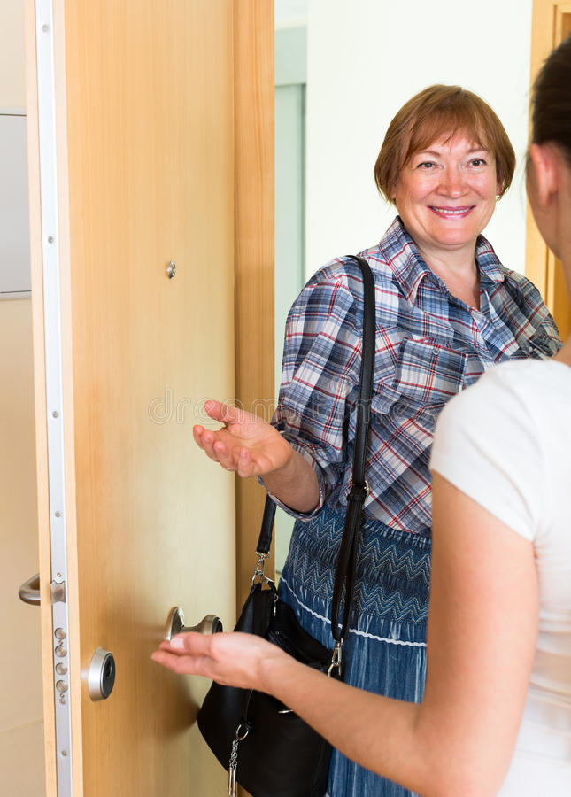 Cheerful greeting of two women at the door. Greeting of two cheerful smiling women standing in the entrance royalty free stock photos