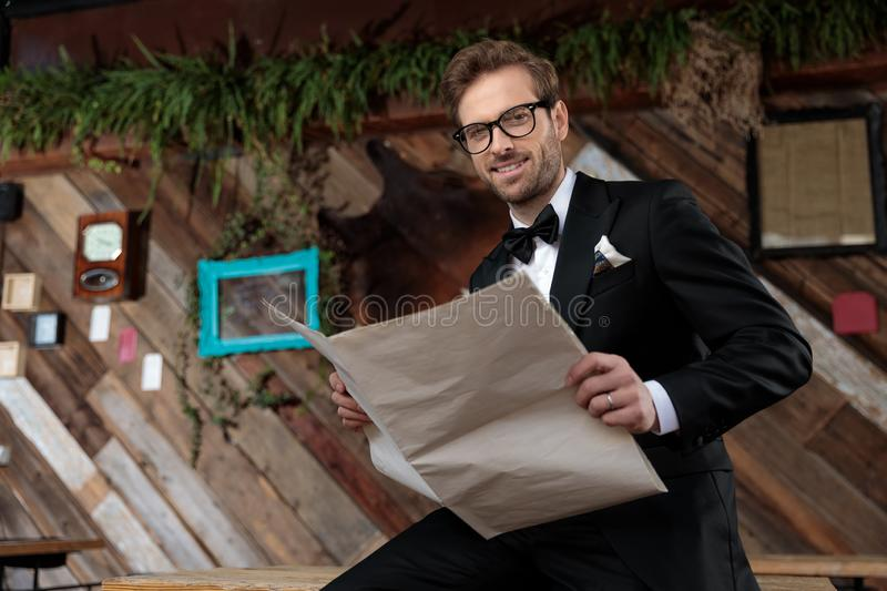 Cheerful groom holding a newspaper while wearing tuxedo stock images