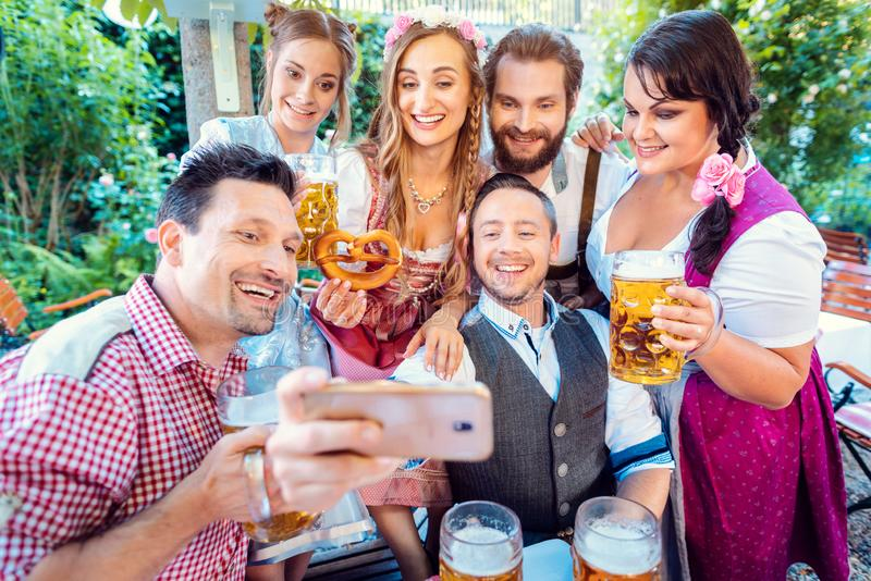 Cheerful group of friends taking a selfie in Bavarian beer garden royalty free stock photography