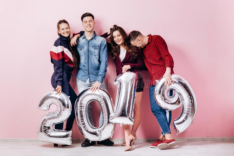 Cheerful group of friends of two girls and two guys dressed in stylish clothes are holding balloons in the shape of stock images