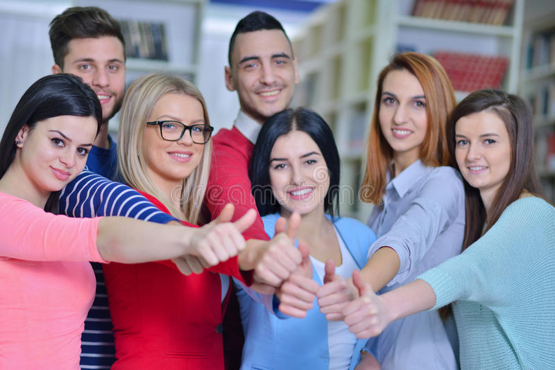 Cheerful group of students smiling at camera with thumbs up, success and learning concept.  stock photography