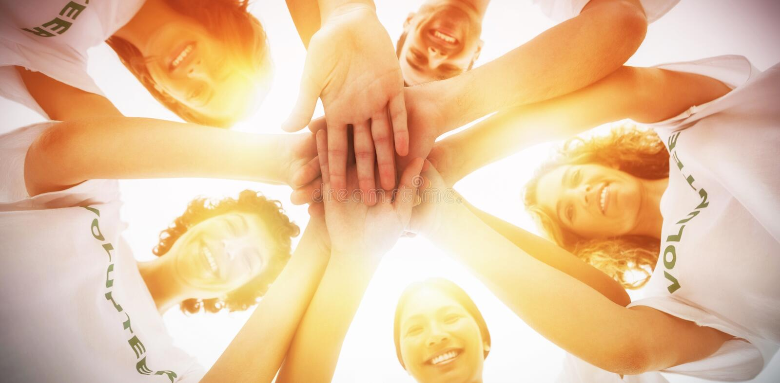 Cheerful group of volunteers putting hands together royalty free stock images