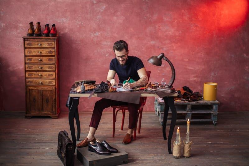 Cheerful guy drawing something at shoe repair shop royalty free stock image