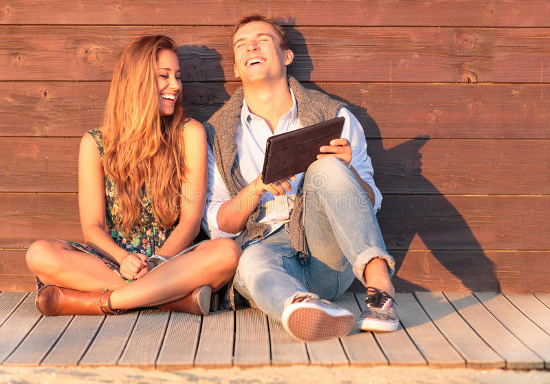 Cheerful guy with girl laugh about video on the tablet. Best friends having fun at the beach with social media and funny contents. stock photo
