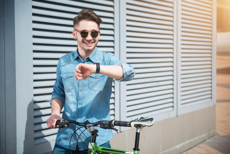 Cheerful guy holding bicycle royalty free stock photo