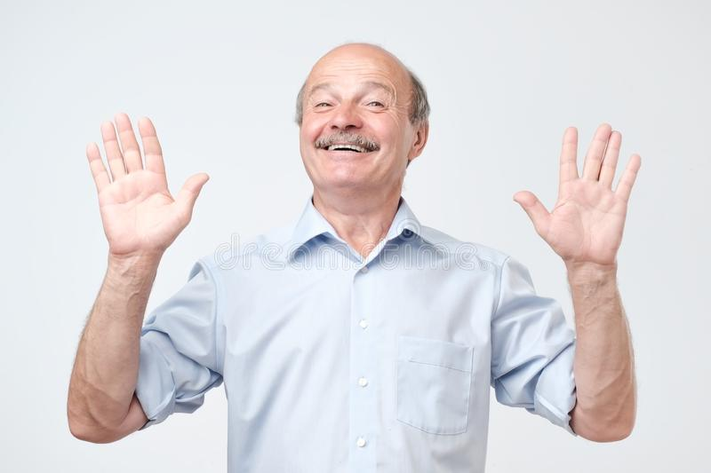 Cheerful guy raises hands as shows being uninvolved, has happy look. Caucasian male gestures in studio royalty free stock images