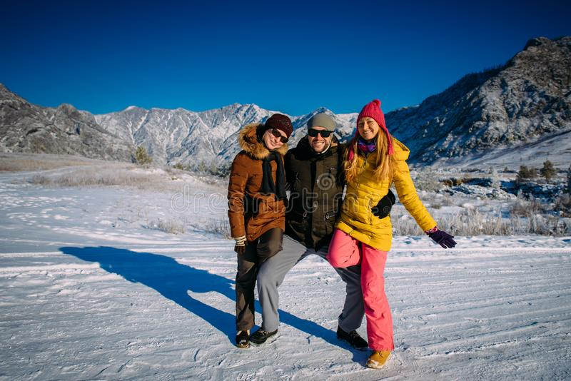 Cheerful guy and two pretty girls posing in colorful winter clothes on the background of snow-capped mountain peaks and blue sky. Young people have fun during royalty free stock photo