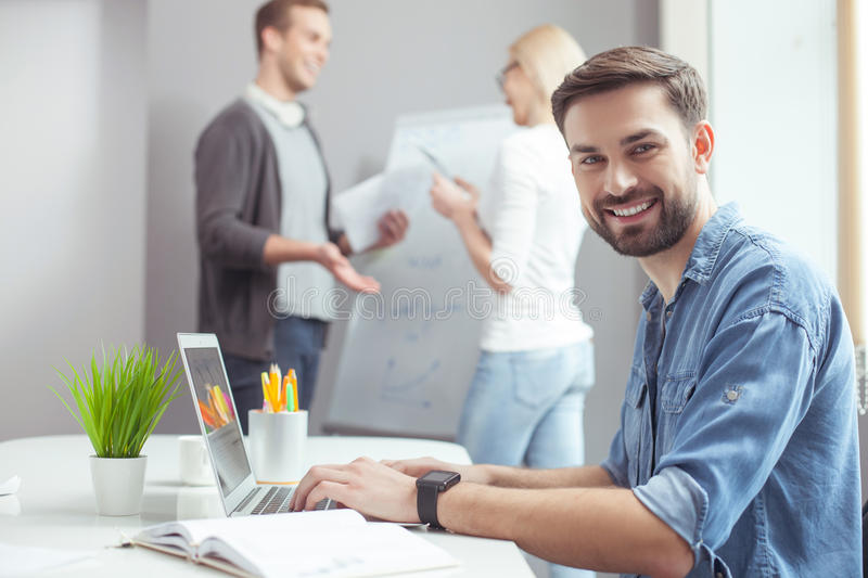 Cheerful guy is working with his team. Handsome young men is using a laptop for work. He is sitting at the desk and looking at camera happily. His colleagues are royalty free stock image