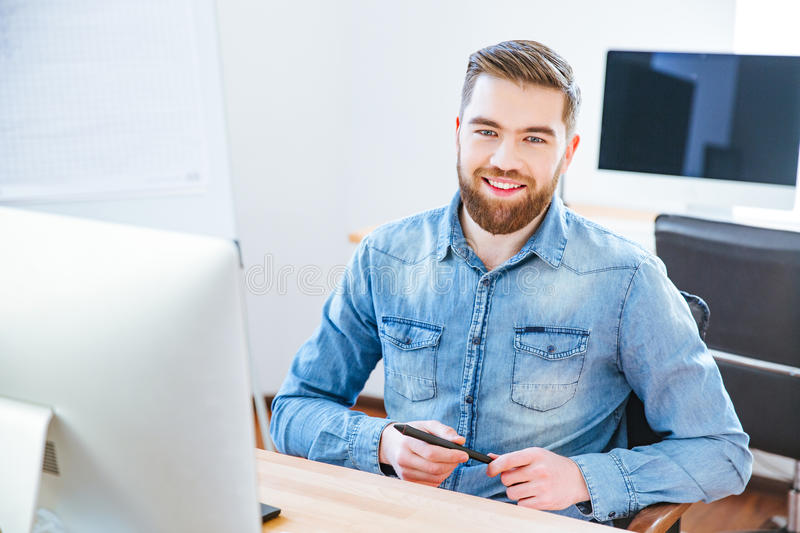 Cheerful handsome designer holding stylus and sitting in office. Cheerful handsome young designer with beard in blue shirt holding stylus and sitting at the royalty free stock images