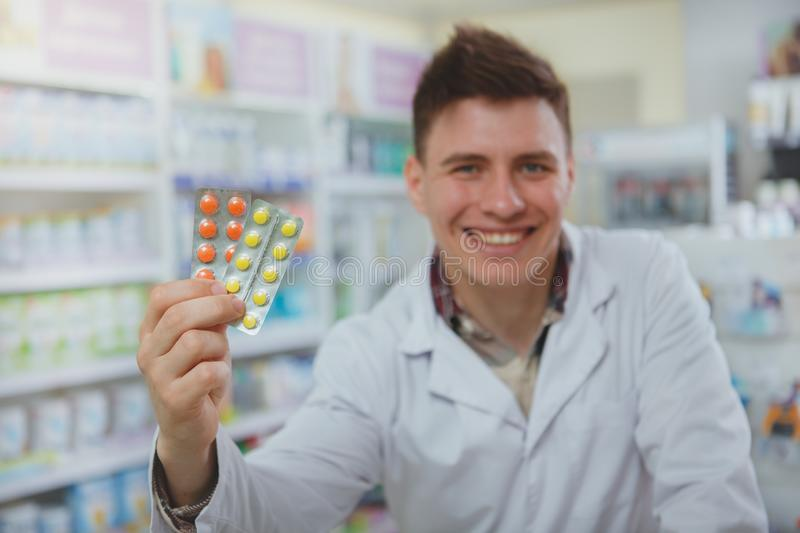 Handsome male pharmacist working at his drugstore stock images