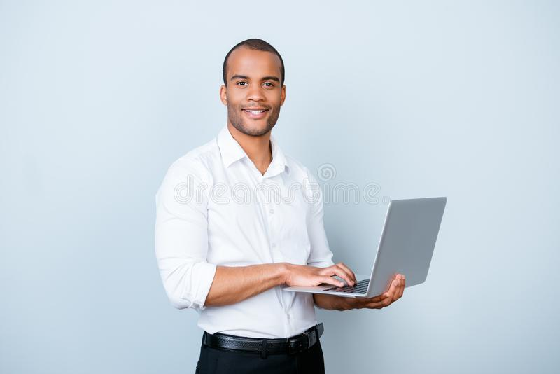 Cheerful handsome young black broker is typing on his laptop, st royalty free stock photo