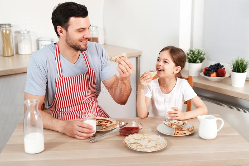 Cheerful handsome young male and little child eat pancakes together, drinks fresh milk, enjoy breakfast at kitchen royalty free stock photo