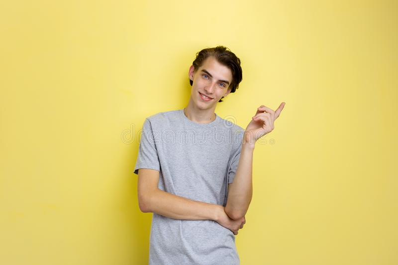 Cheerful handsome young thin dark-haired guy with blue eyes wearing gray t-shirt pointing left, standing against yellow. Background stock photos