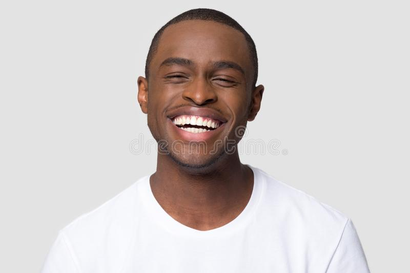 Cheerful happy african millennial man laughing isolated on studio background royalty free stock images