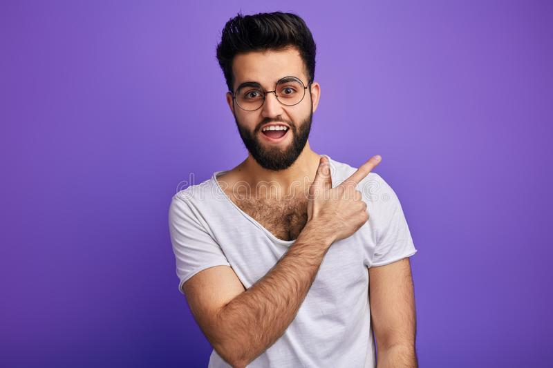 Cheerful happy bearded man indicates happily at somewhere stock photography