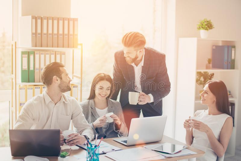 Cheerful happy colleagues in smart clothes having nice conversation during the break in office smiling and drinking coffee stock photography