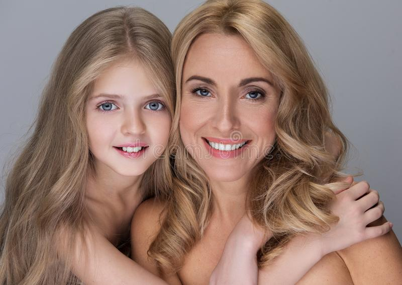 Cheerful happy family is posing with naked shoulders. My best mom. Portrait of cute little daughter is hugging her charming middle-aged mother while standing royalty free stock image