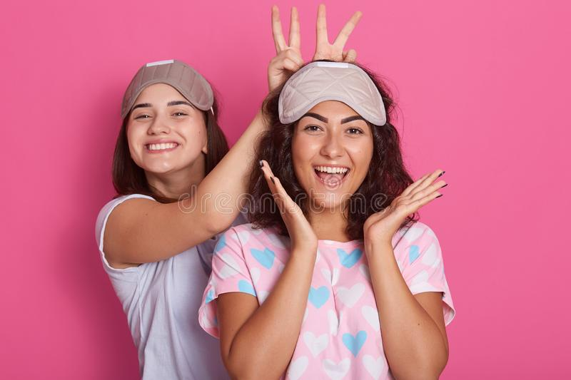 Cheerful happy girls in pajamas and sleep masks rests both hands over the mask and have fun showing tongue grimacing. Studio close royalty free stock images