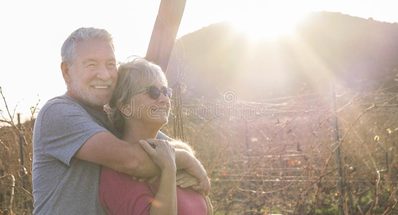 Cheerful and happy healthy people couple of senior old caucasian man and woman in outdoor leisure activity together hugging and. Cheerful and happy healthy stock photo